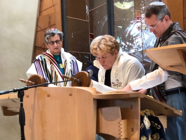 Marie Pedersen chants Torah as Rabbi Lisa and Cantor Juval look on. Photo by Ray Eelsing.